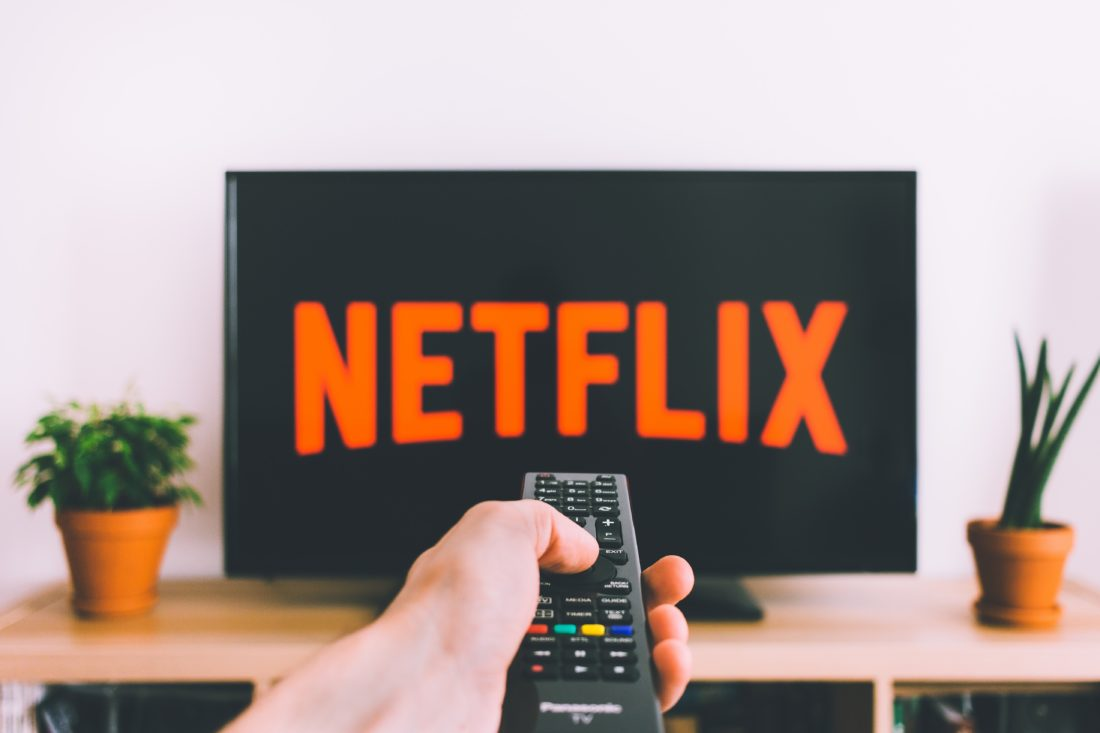 hand holding remote pointed at tv with netflix logo