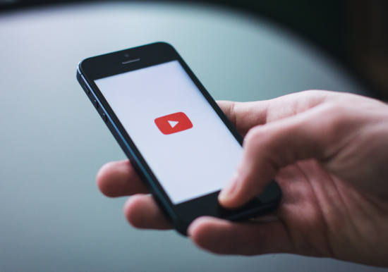 hand holing iPhone with youtube logo